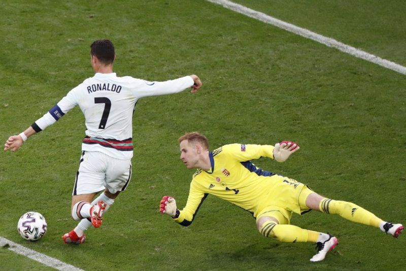 Portugal\'s forward Cristiano Ronaldo scores his team\'s third goal past Hungary\'s goalkeeper Peter Gulacsi (R) during the UEFA EURO 2020 Group F football match between Hungary and Portugal at the Puskas Arena in Budapest on June 15, 2021